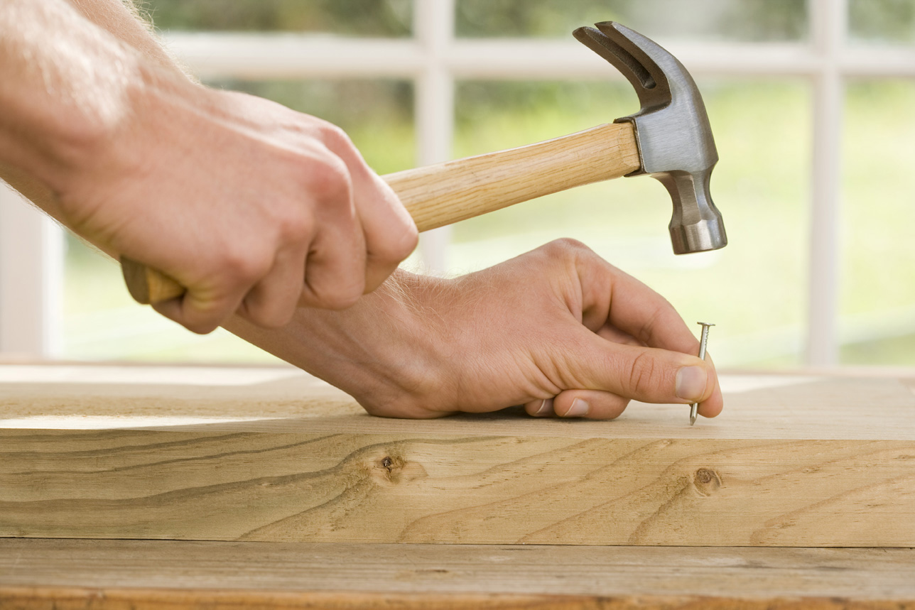 Hands hammering nail into wood