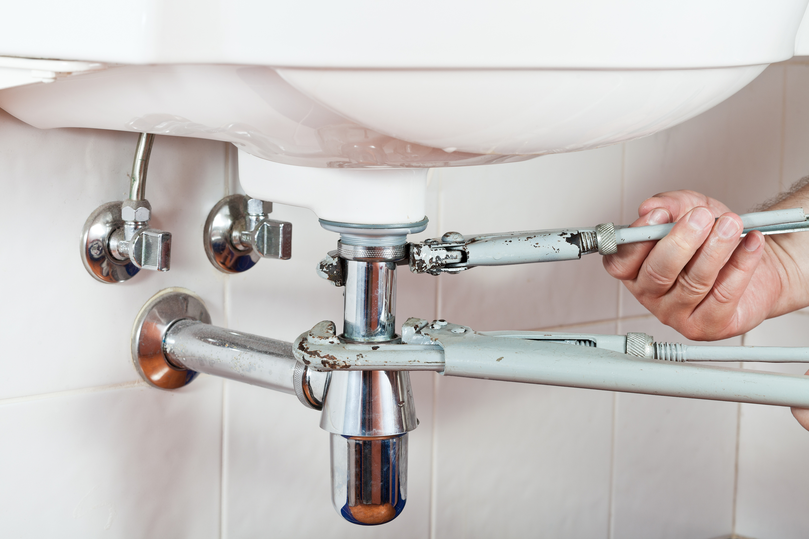 plumber repairing sink drain by pipe-wrenches close up
