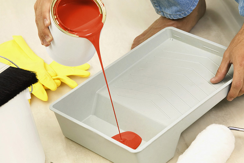 Barefoot man pouring red paint into roller pan, close-up